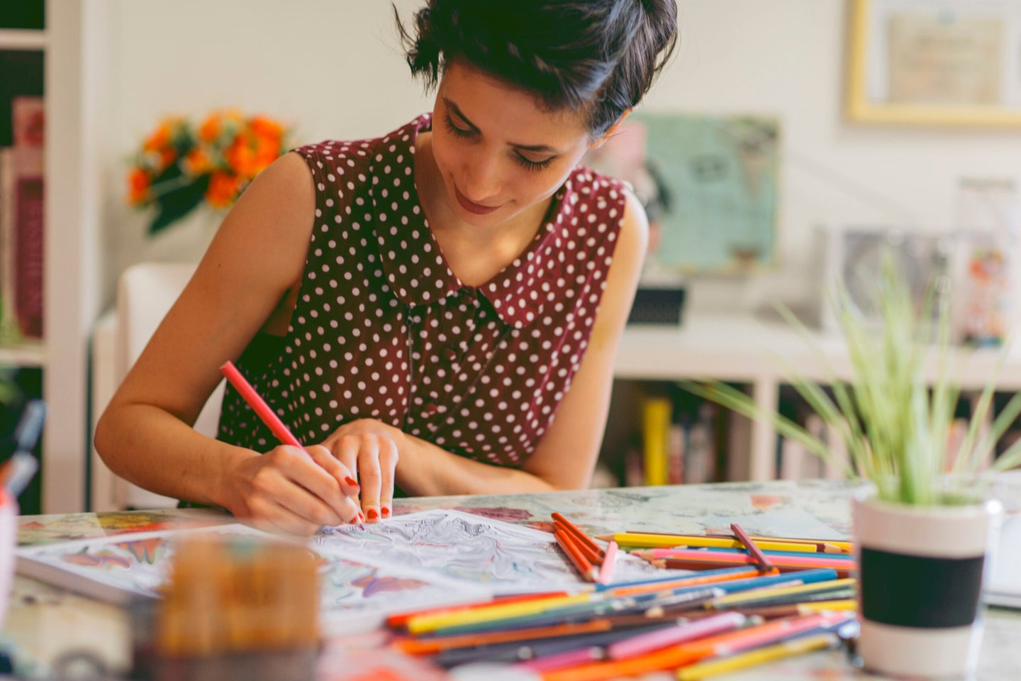 Young smiling woman coloring book for adults in her office or apartment, Enjoy coffee break while coloring book for adults. Adults Coloring Book.