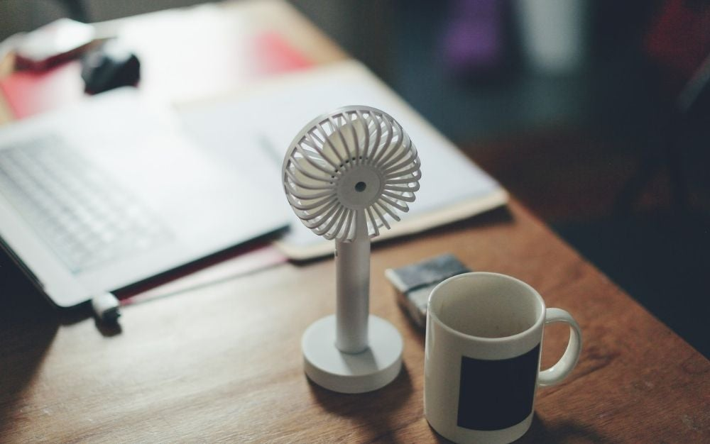 A white mini desk fan behind a white cup of coffee and some letters behind, all on top of the wooden desk.