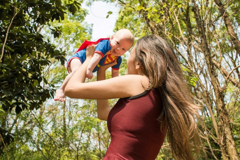 Woman holding a baby in a Superman outfit