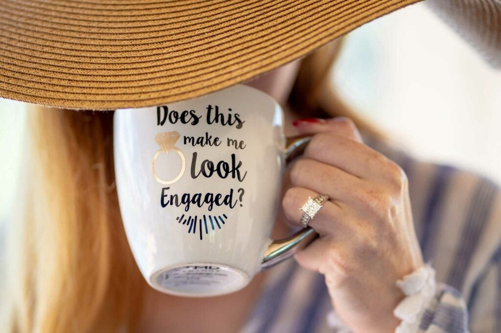 Woman wearing a giant hat drinking from a mug