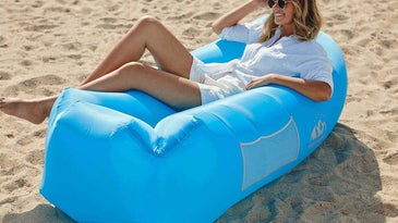 Woman sitting on an inflatable couch on the beach