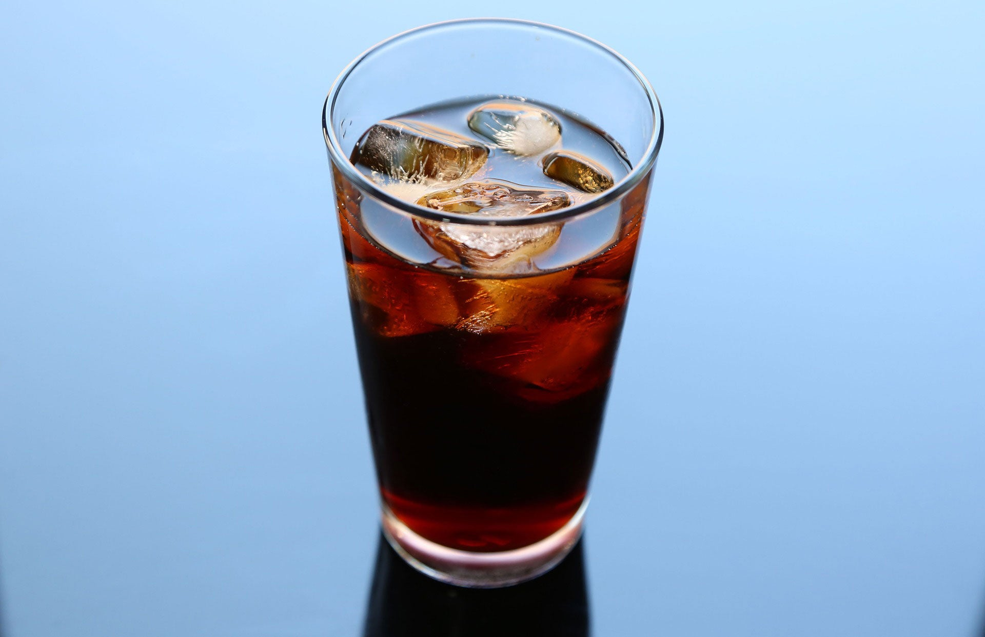 Glass of cold brewed coffee on blue background