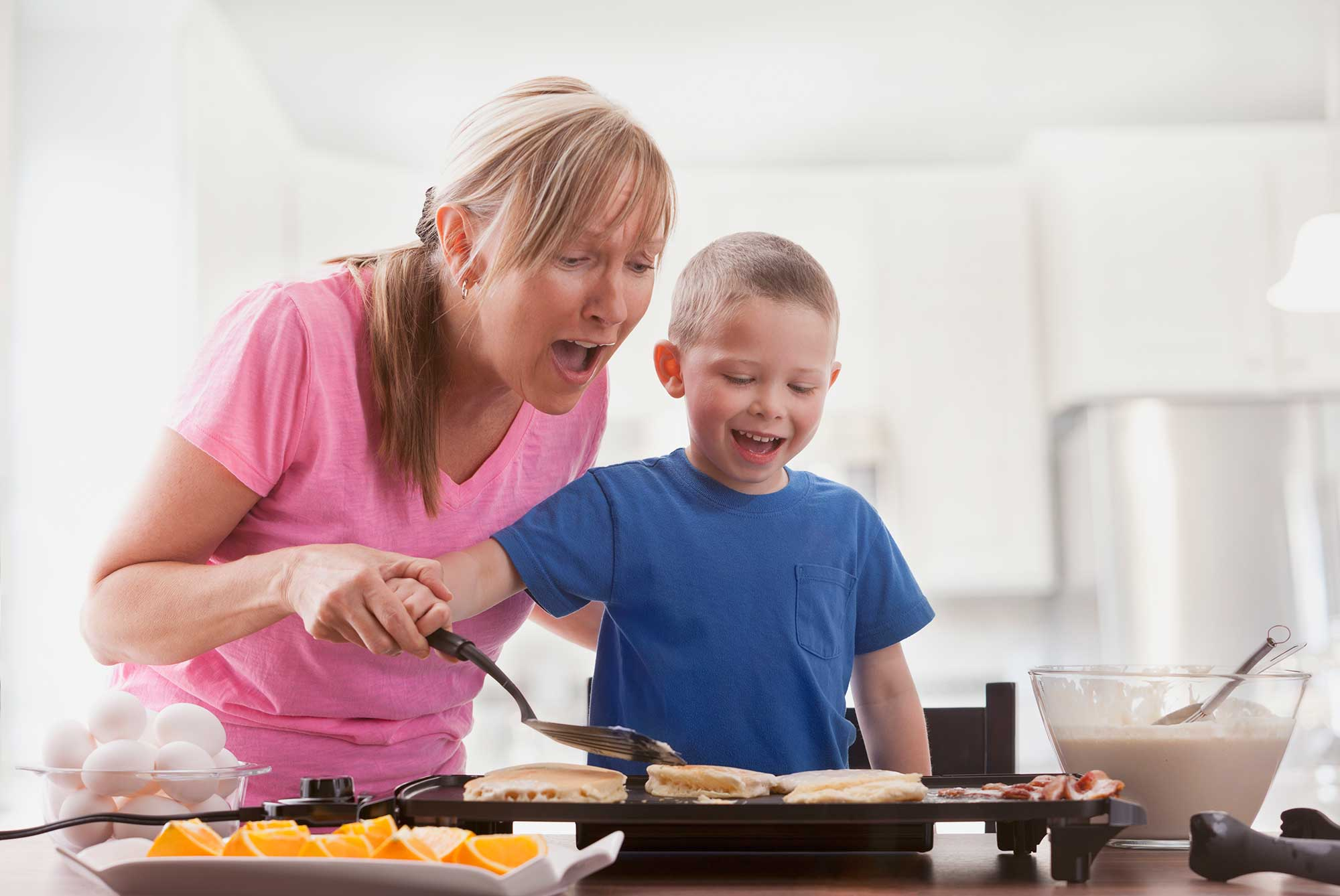 Mother and son making pancakes