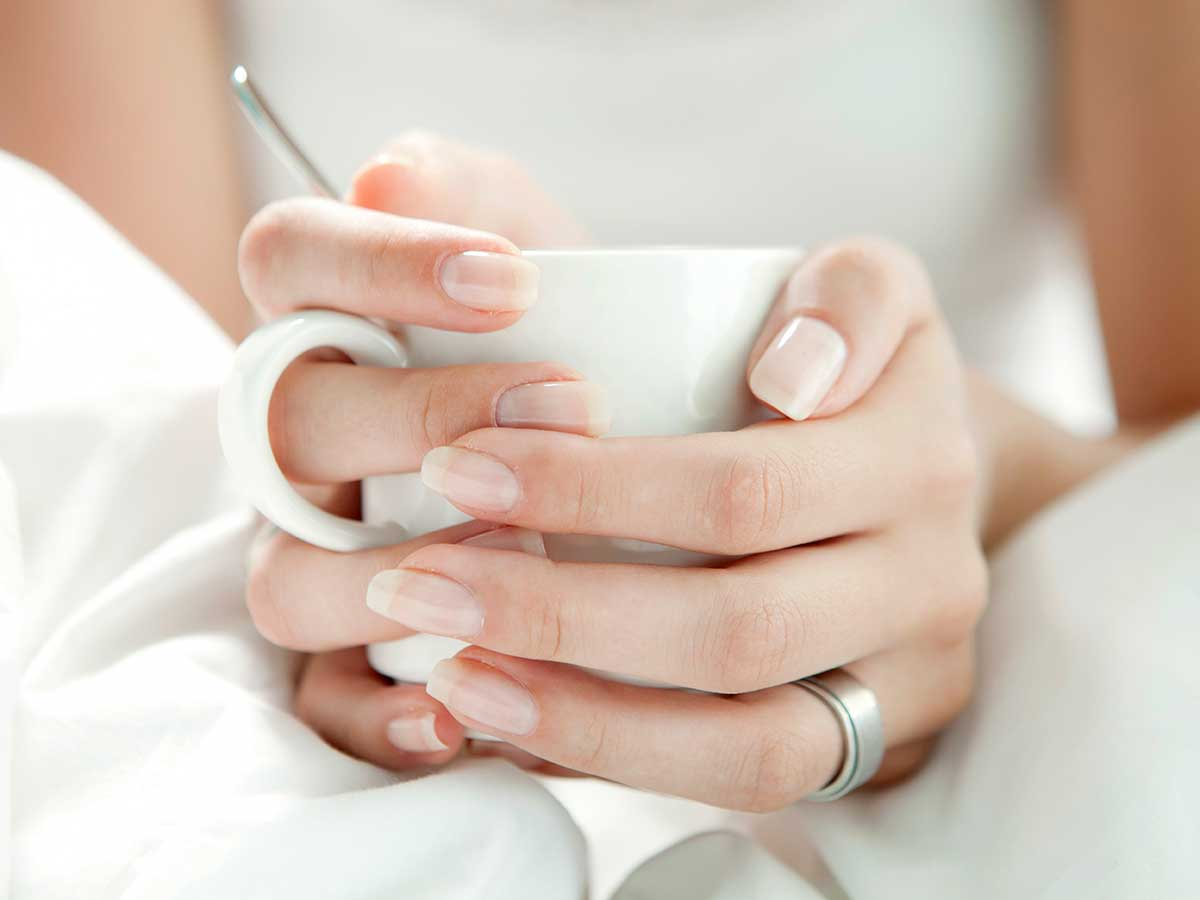 woman with good hands holding a mug