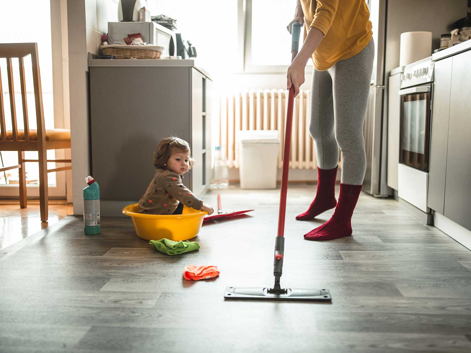 Woman mops the floor with spray mop
