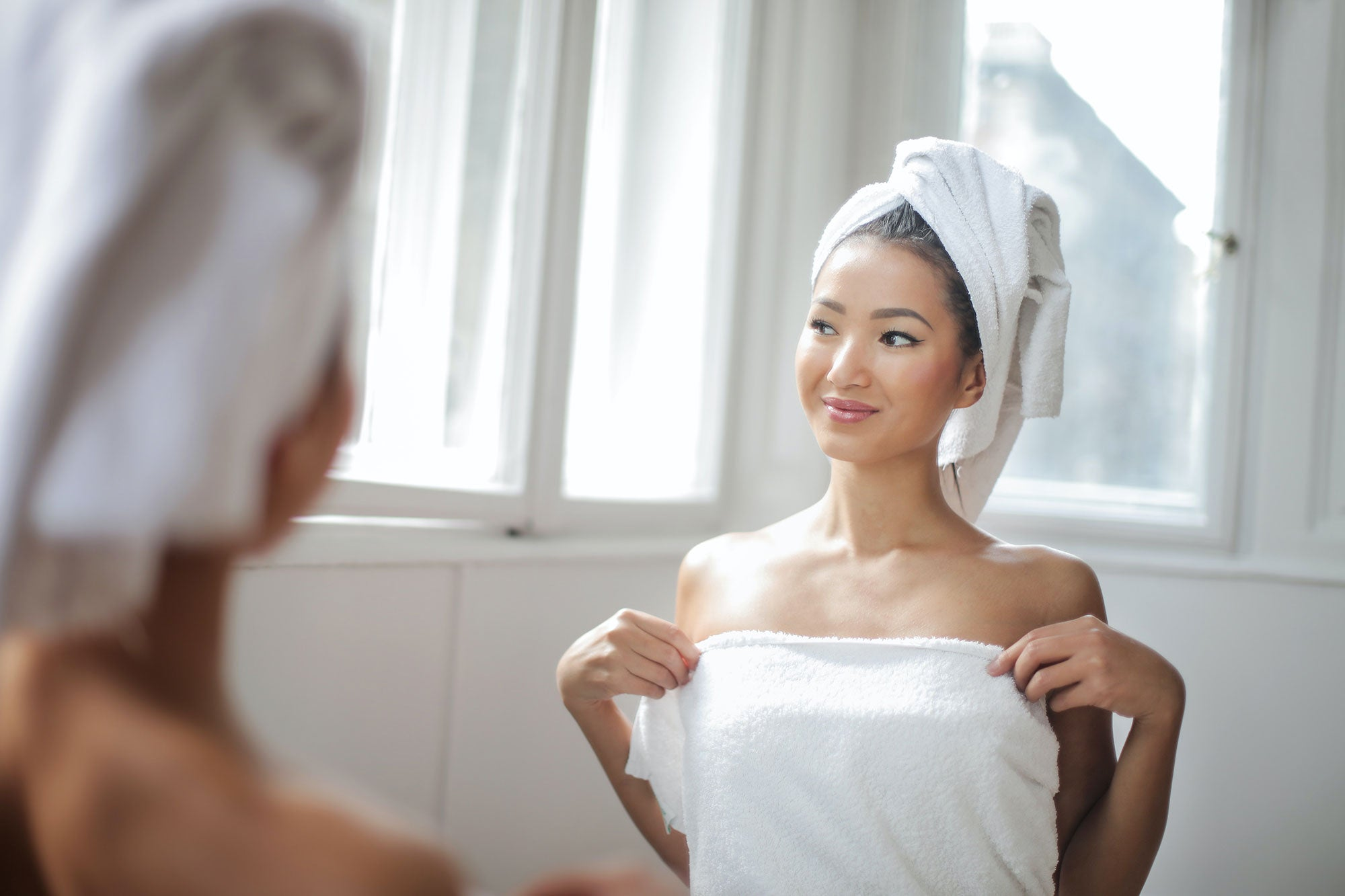Woman in bath towel looking at herself in the mirror