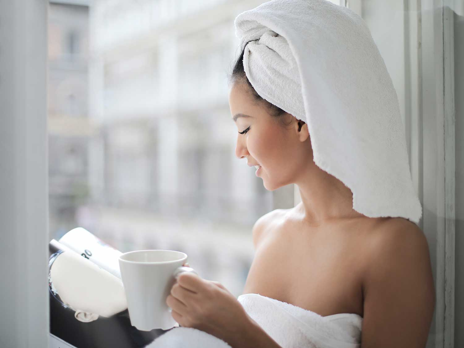Woman reading magazine with cup of coffee after morning shower.