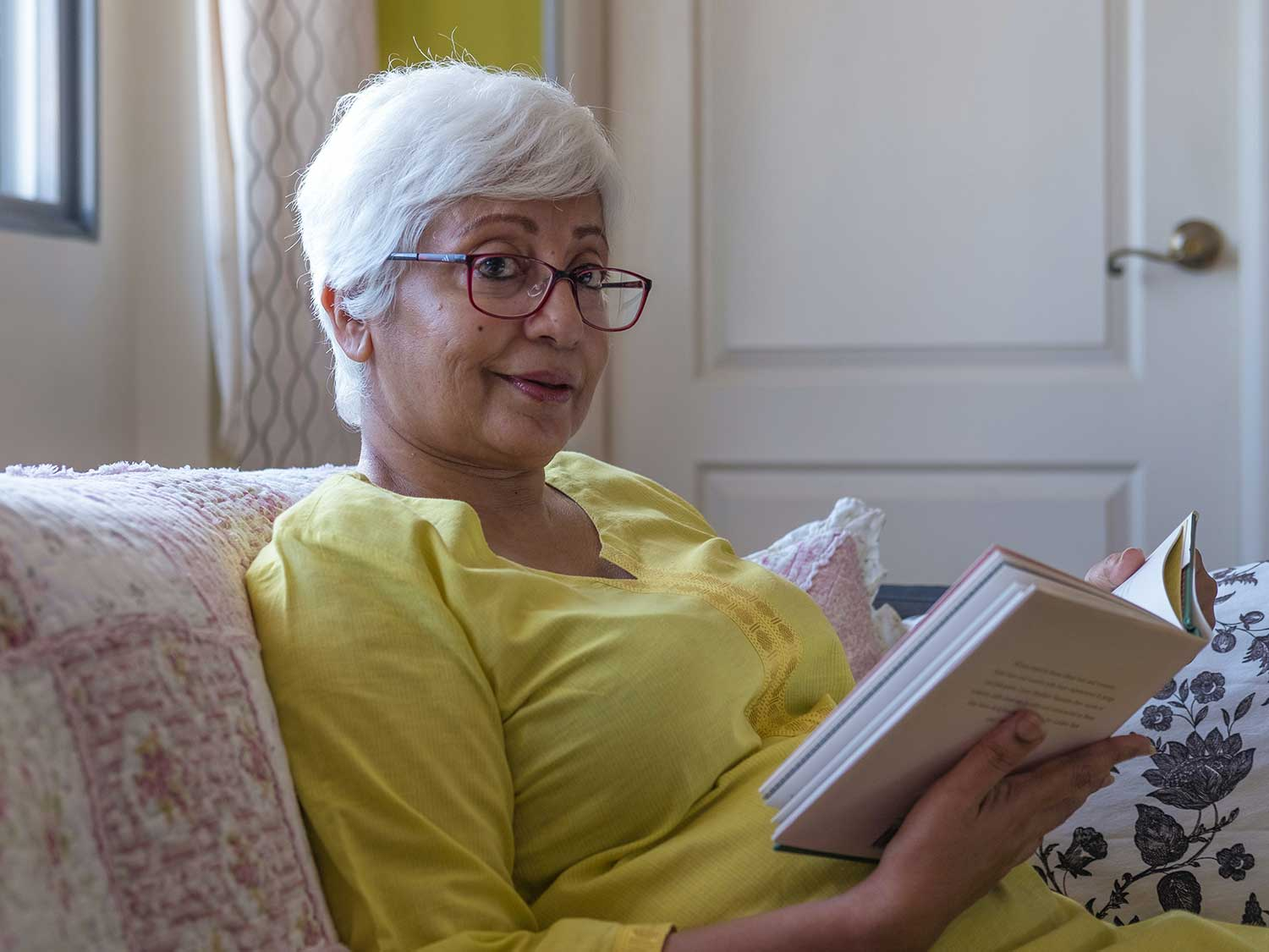 Woman reading book with reading glasses.