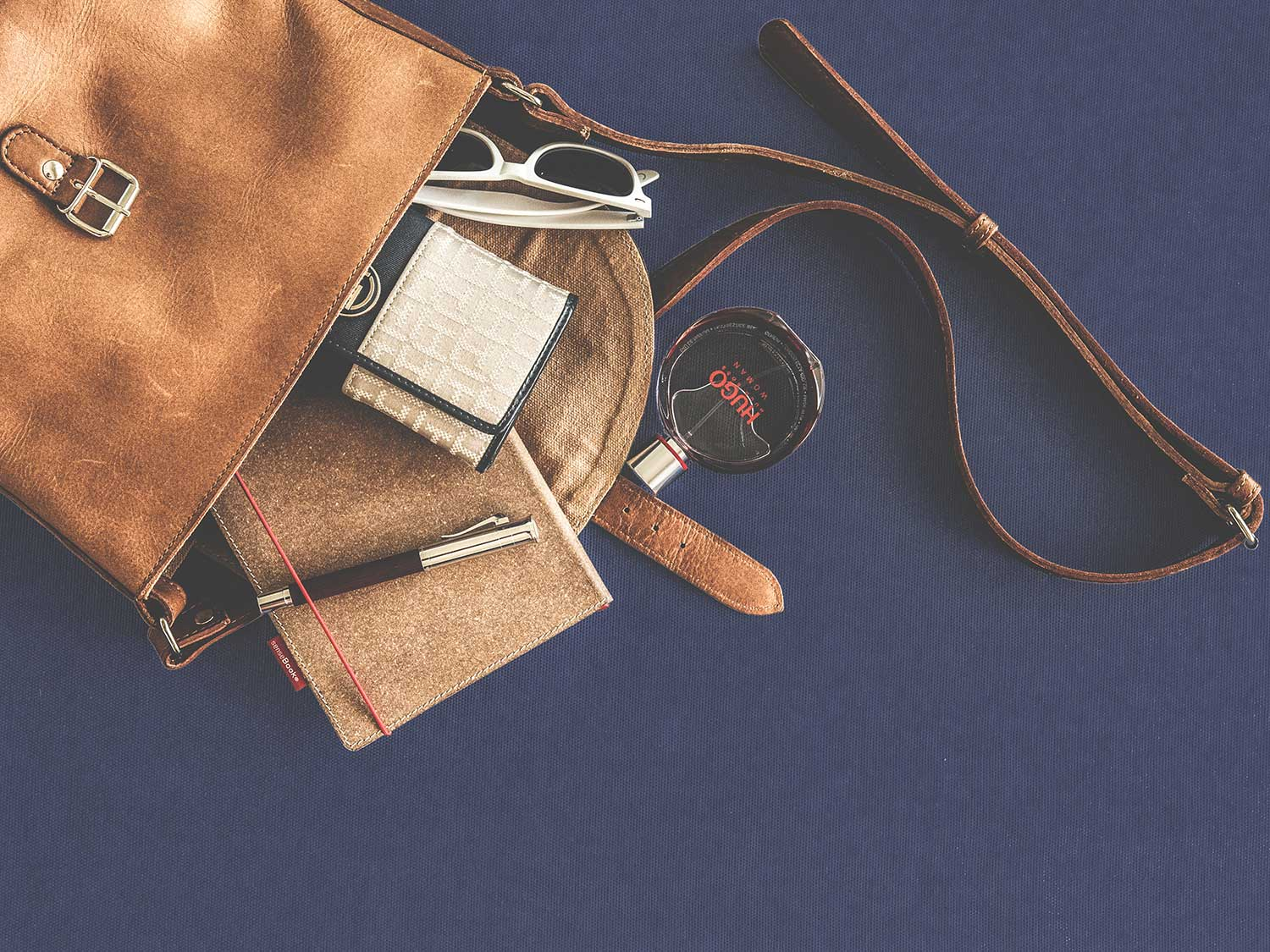 Items in brown leather crossbody bag