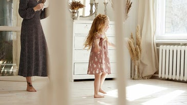 Little girl and her mother in a sunlight bedroom