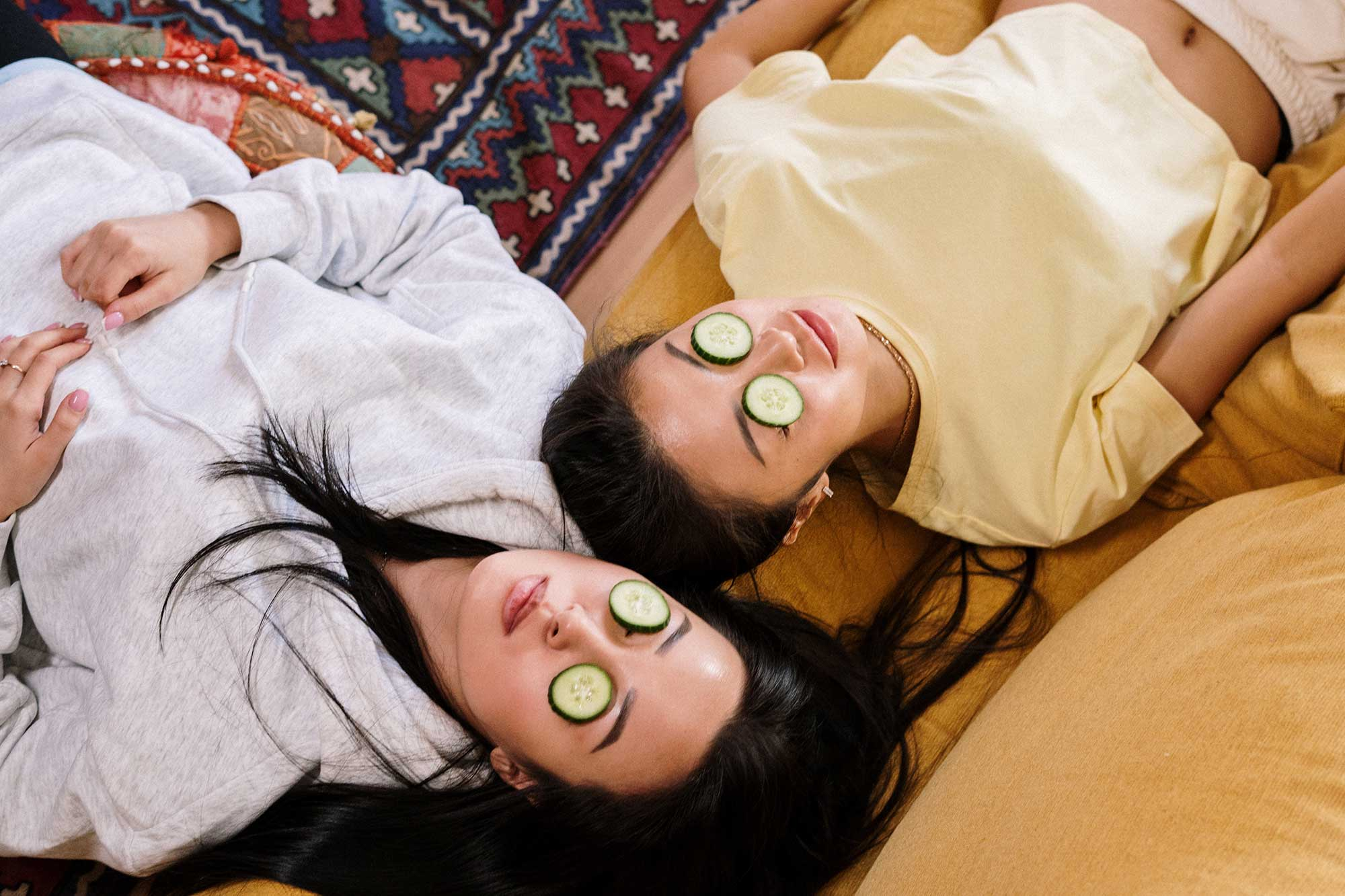 Two women lying down with cucumbers over their eyes