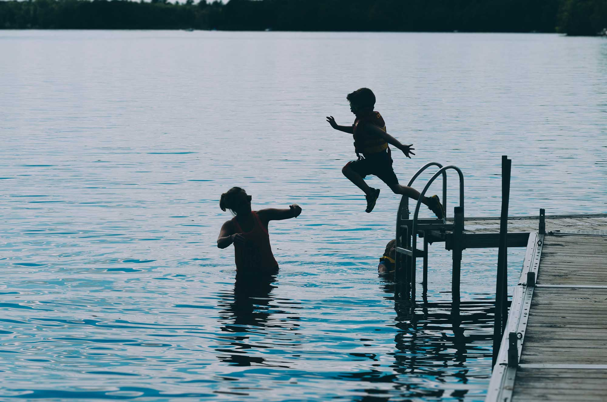 Child jumping off dock and into a lake