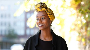 Attractive black woman wearing a yellow headwrap.