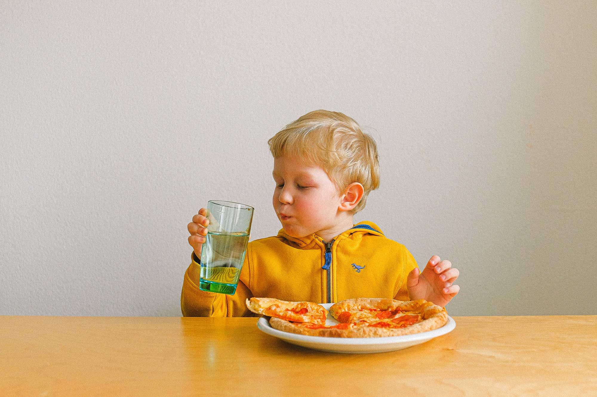 Toddler drinking out of a cup and eating pizza