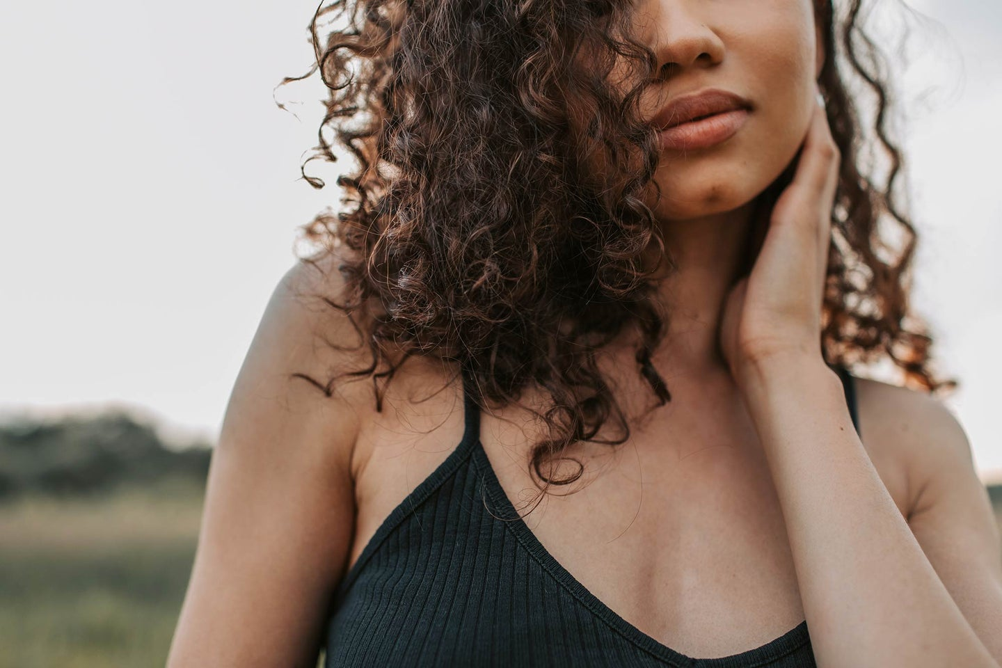 Close up of a women with curly hair wearing a black tank top