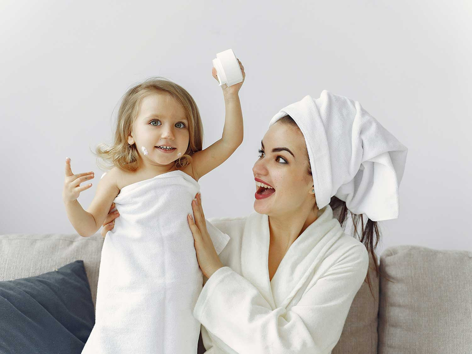 Girl and woman wrapped in towel and spa robe.