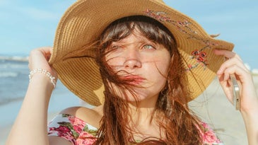 Woman on the beach wearing a large sunhat