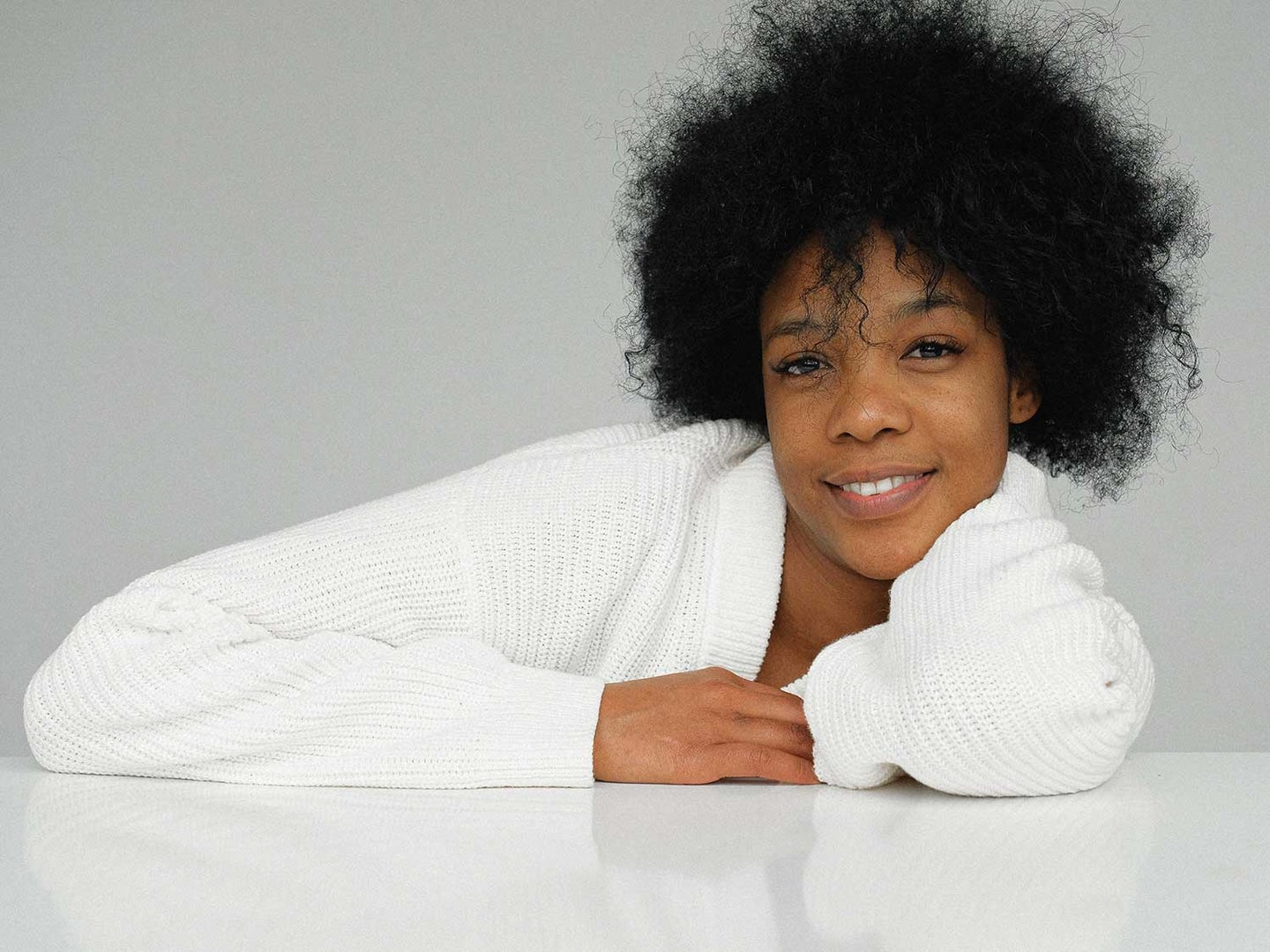 Woman with beautiful, radiant skin leaning  on table.