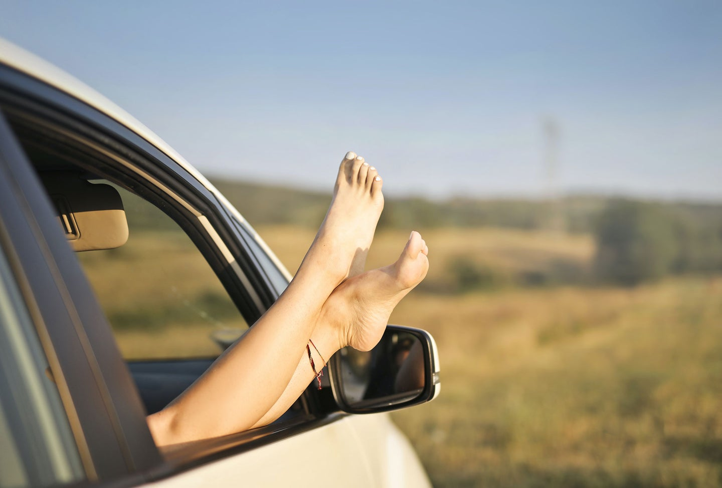 Person's bare legs hanging out of car window