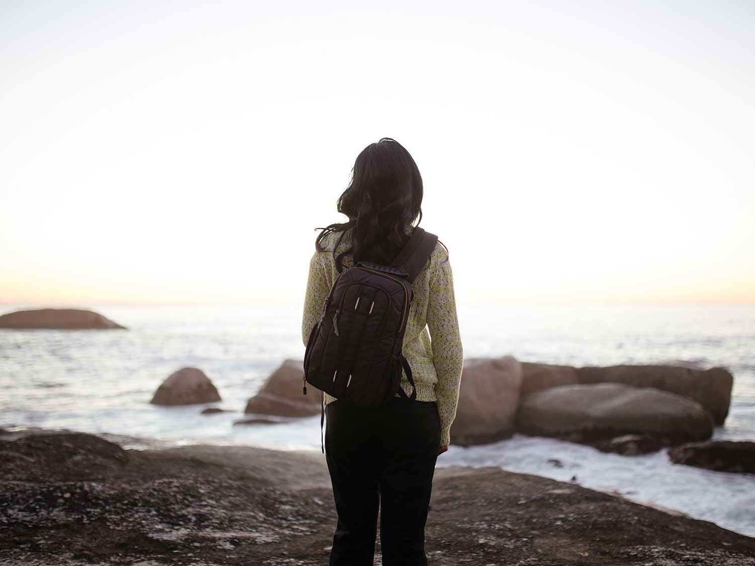Woman carrying cooler backpack on beach.