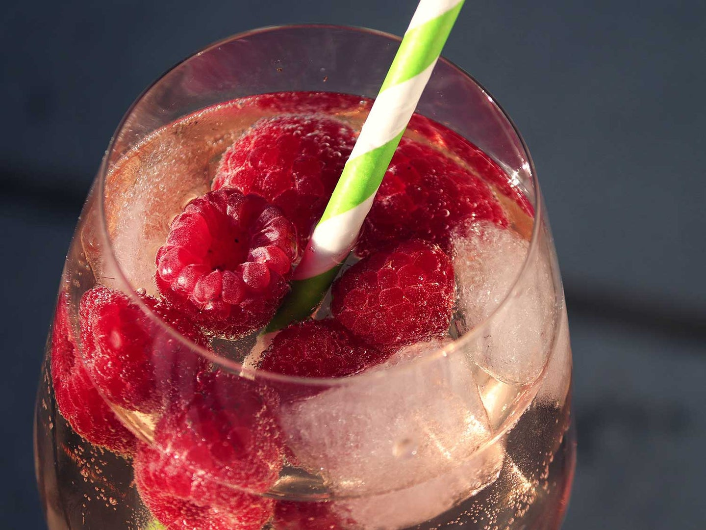 Raspberries in drink with straw.
