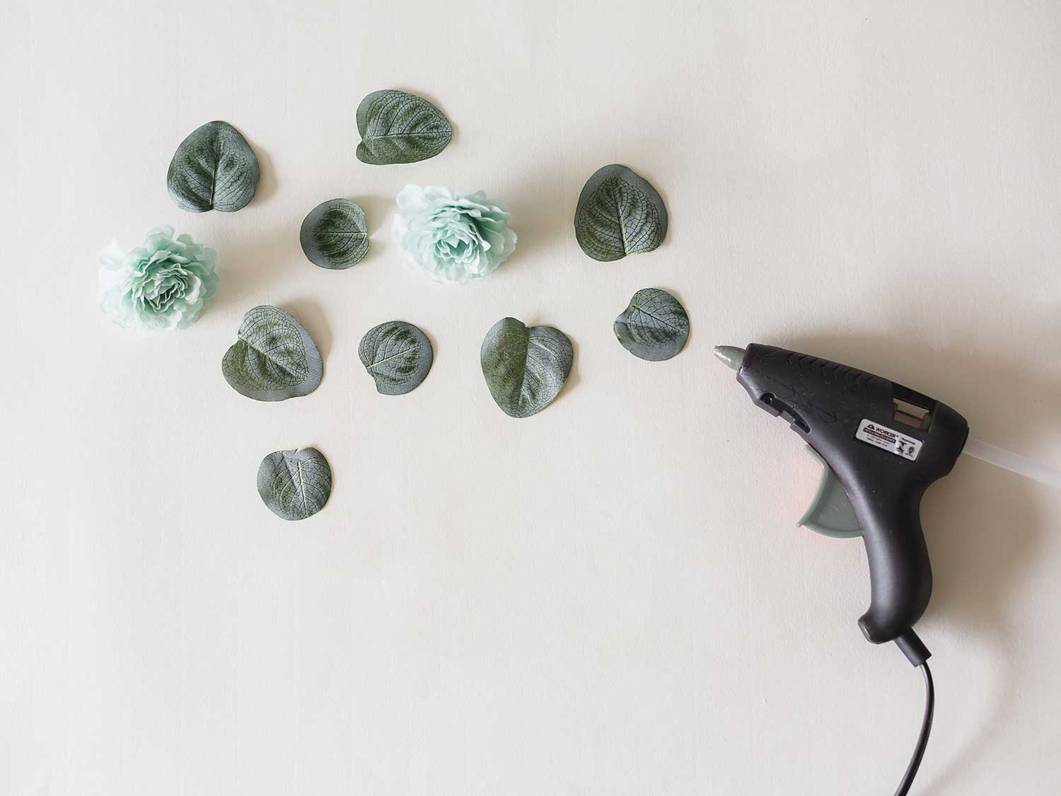 Securing fabric leaves with hot glue gun.