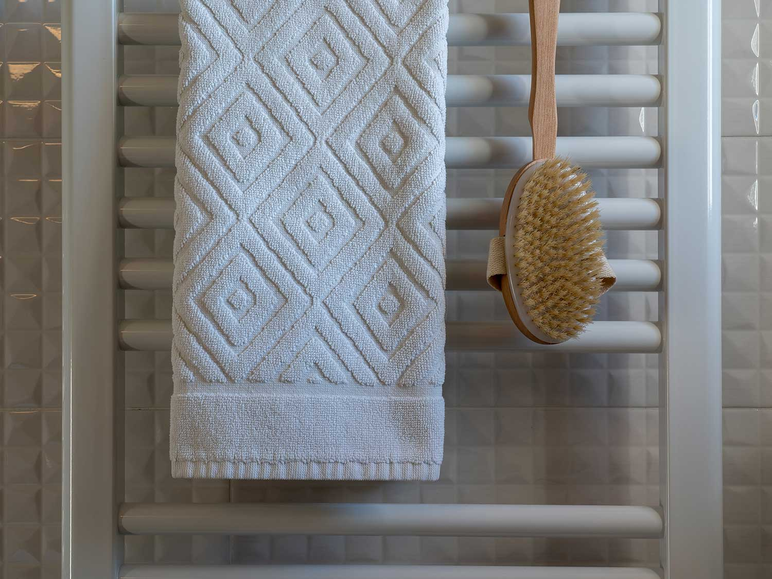 Shower scrubber and towel hanging in bathroom.