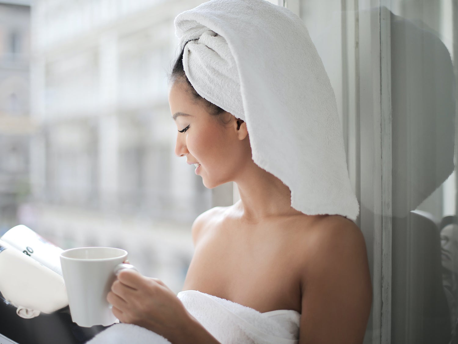 Woman reading with cup of coffee and wearing microfiber hair towel out of the shower.