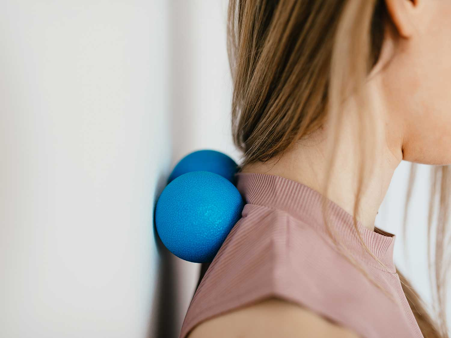 Woman massaging neck with massage balls against wall.