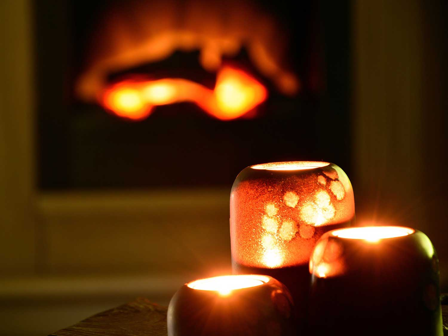 Candles in front of fire.
