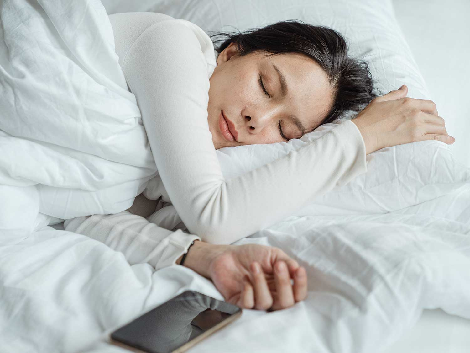 woman sleeping on pillows and blankets
