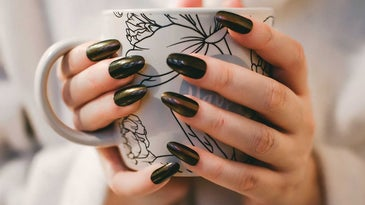 Woman with black manicure holds coffee cup.
