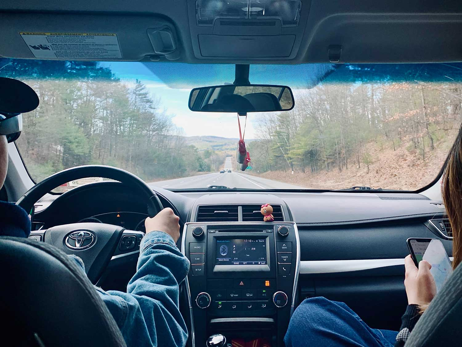 Man and woman driving in car on road trip.