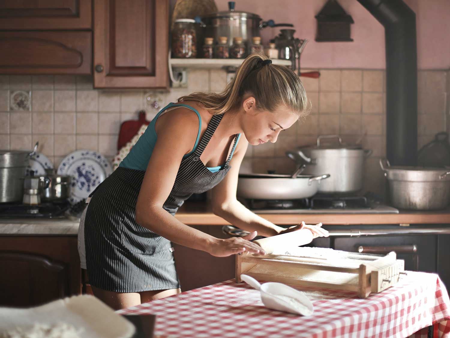Woman rolling out pie dough while wearing kitchen apron.