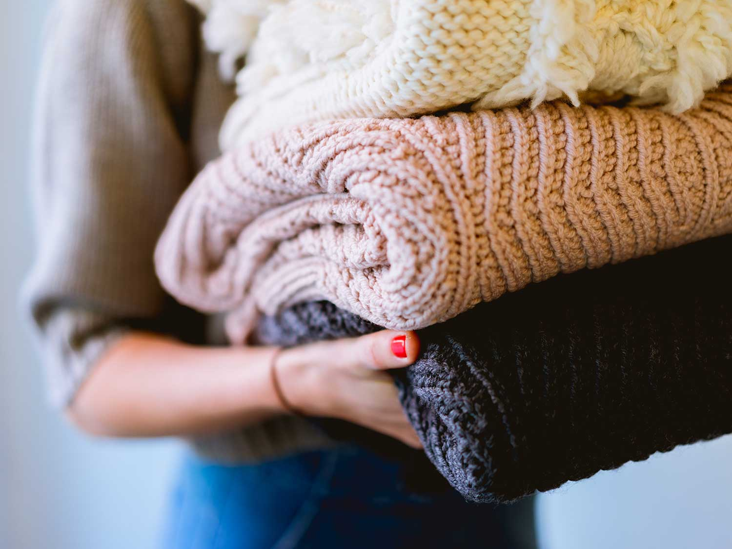 woman carrying woven blankets