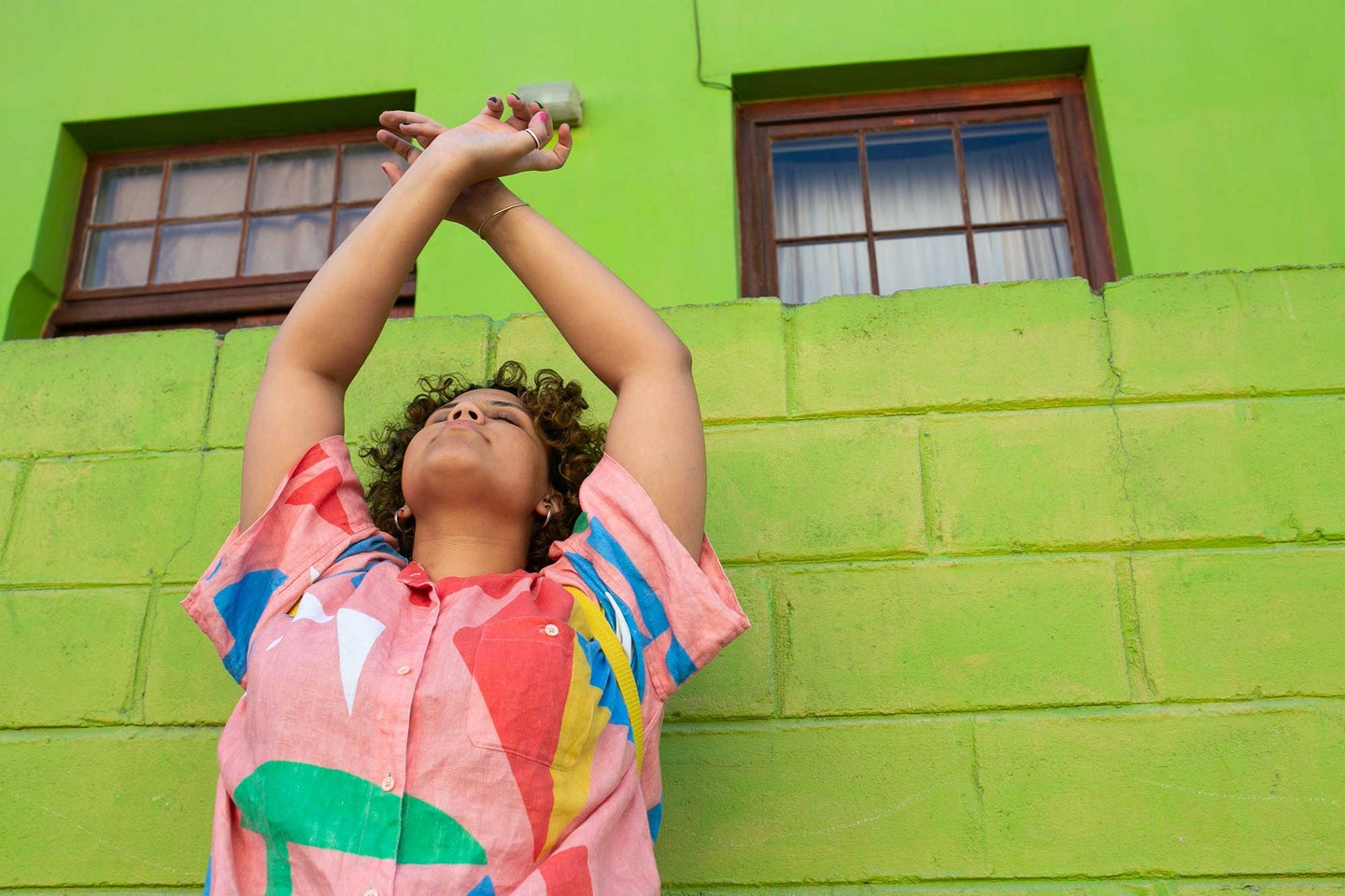 Woman with raised arms in front of a neon green brick wall