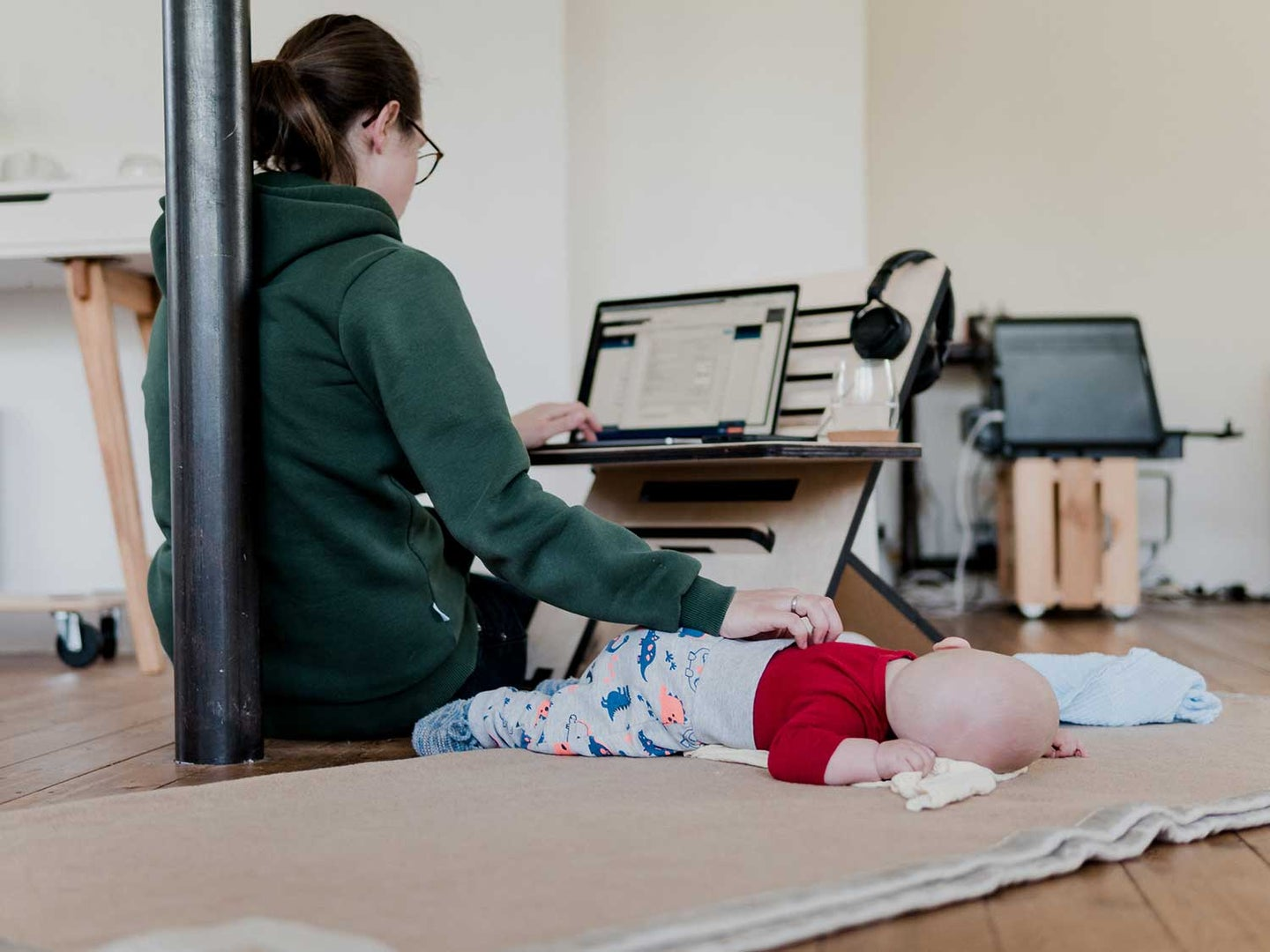 Woman sitting with lapdesk on floor with baby.