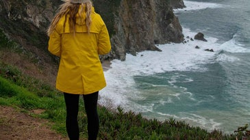 Woman wearing rain jacket standing at the edge of a rocky cliff above water.