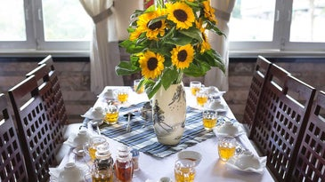 Table set with teacups, silverware, vase with flowers, and tablecloth.