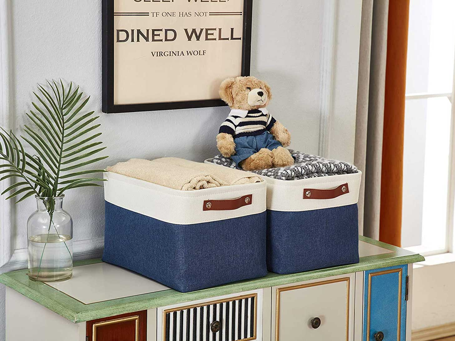 Storage cubes sitting on top of dresser with stuffed teddy bear and blankets.