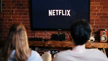 Man and woman watching Netflix on 65-inch TV.