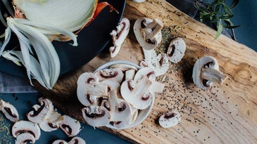 Mushrooms on top of wooden cutting board.