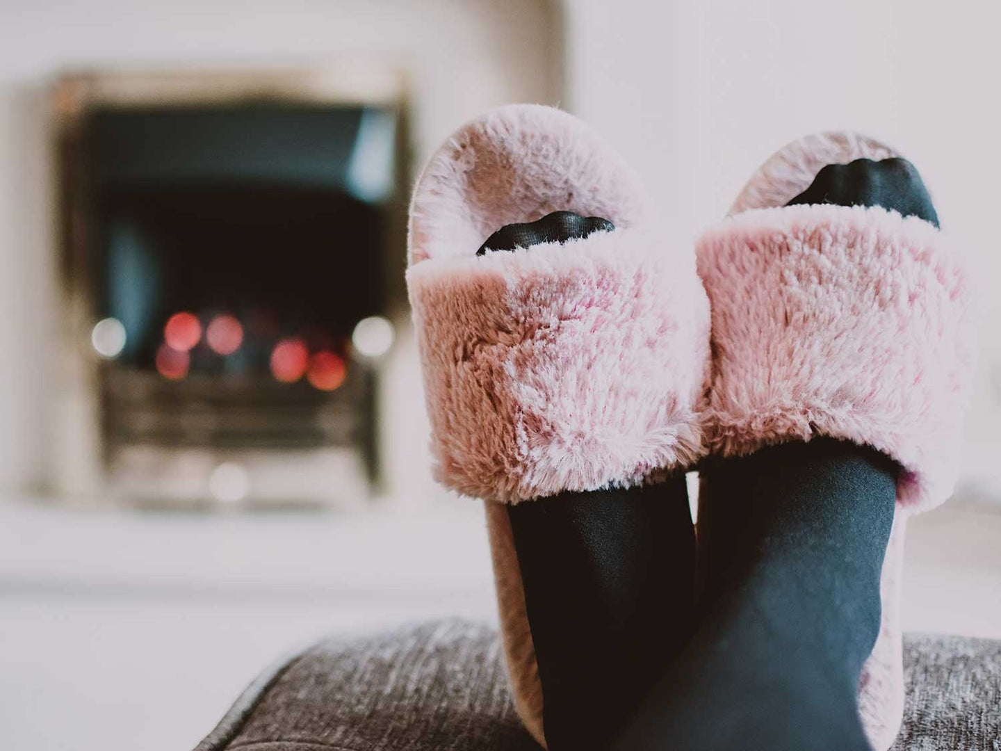 Woman wearing tights and slips while relaxing in front of the fireplace.