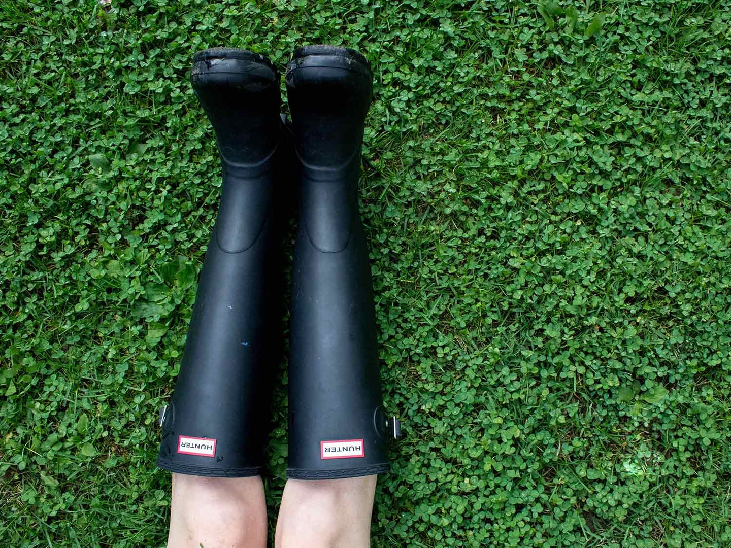 Wearing rain boots while stretched out on lawn.
