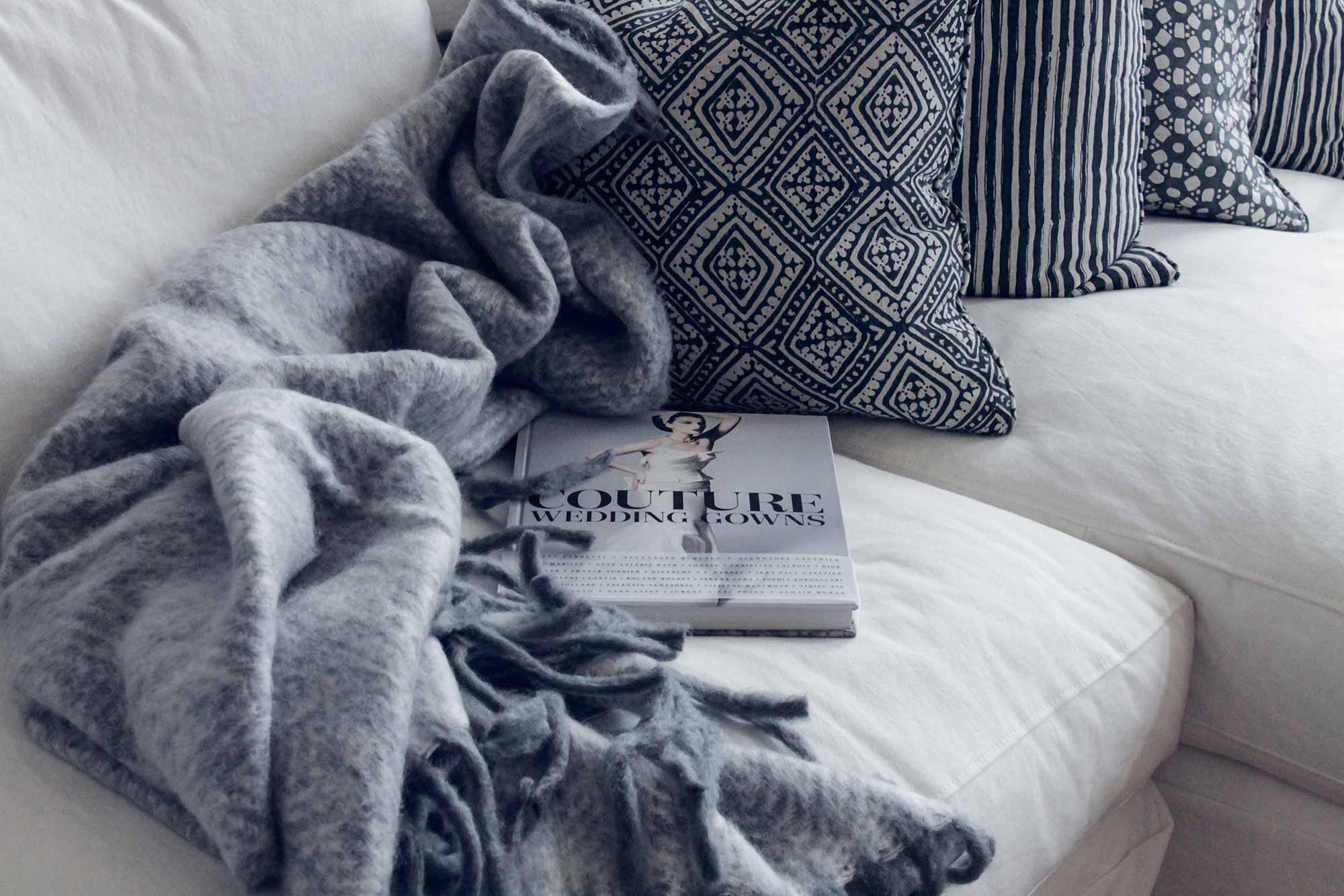 Cozy couch with blanket and book