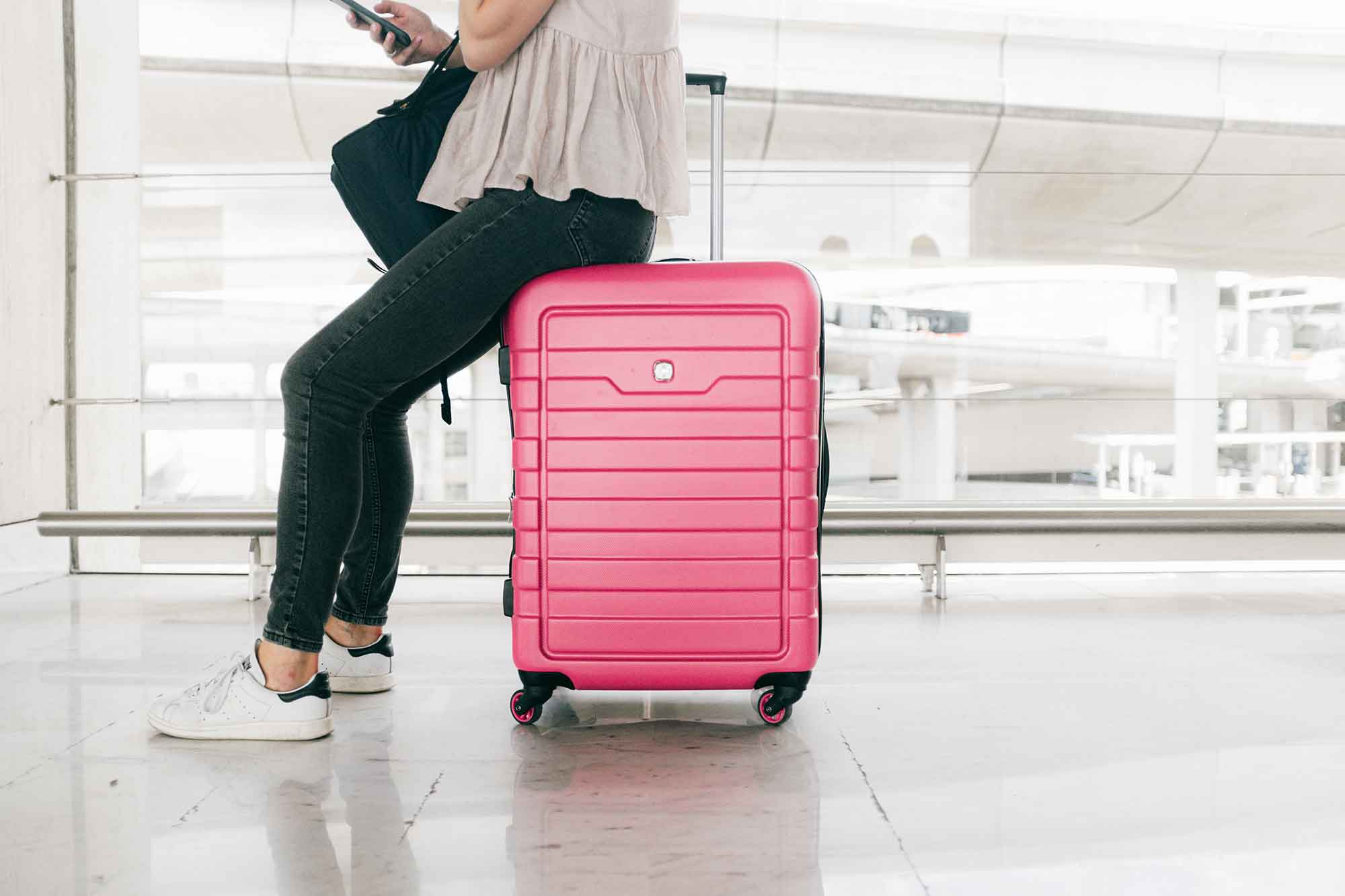 Woman sitting on top of pink luggage