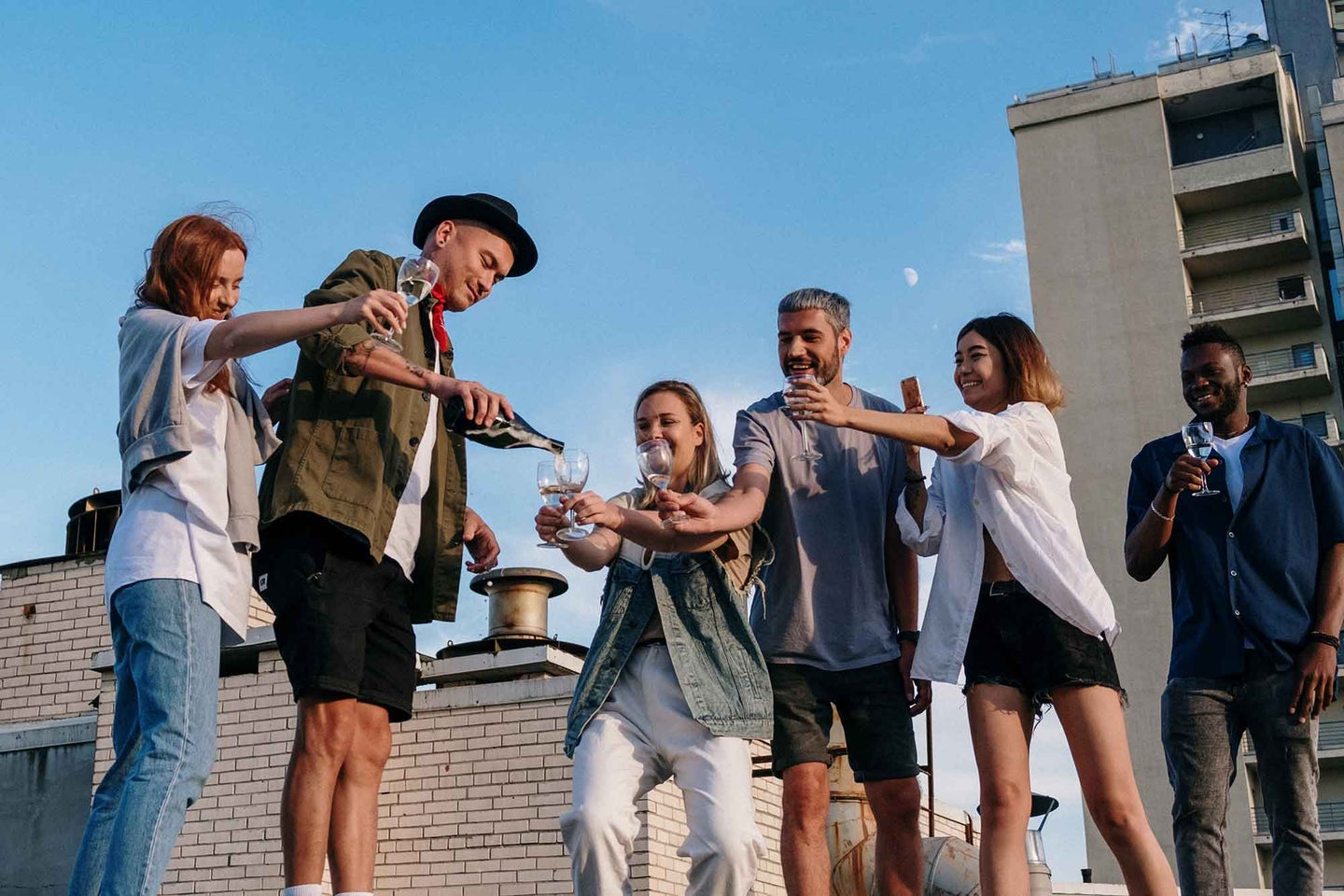 Group of friends drinking wine on a rooftop