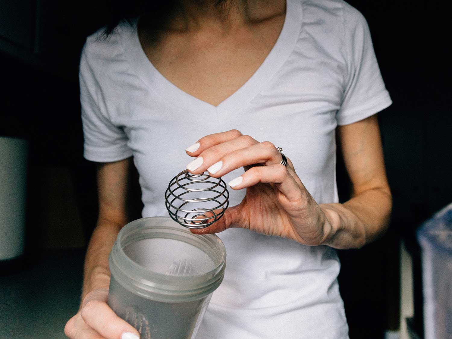 Woman using shaker bottle for protein mix or smoothie.