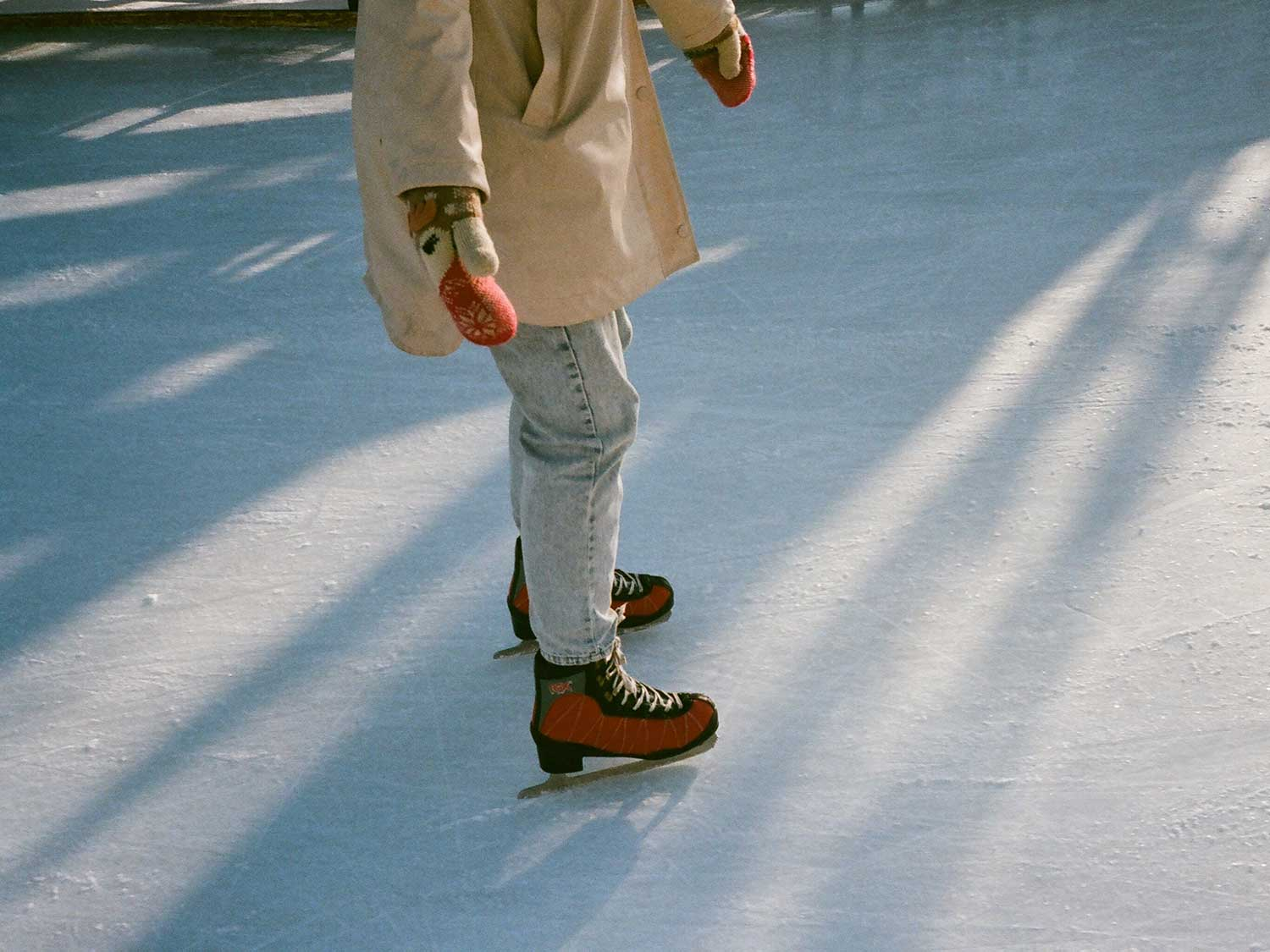 Woman ice skating with gloves warmed with hand warmers.