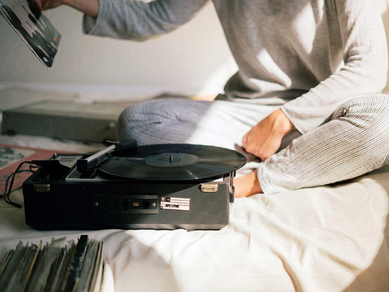 Using record player on bed.